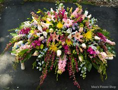 Mixed spring casket spray designed by Max's Flower Shop.