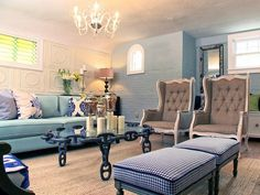 This traditional living room was built in 1920s and has a style that blends the old with the new. Classic furniture features timeless fabrics and a glamorous glass chandelier highlights the space. Vintage tiles are used to create a wallpaper effect on one wall, while the other walls are exposed brick painted a blue-gray.