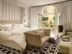 Love that curtain above the bed, the tufted loveseat and the graphic rug.         Francisco Garden Court Hotel  refurbished by very talented Spanish designer Pablo Paniagua. For more of his work visit  Nuevo Estilo.