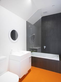 A mostly black-and-white bathroom with a colorful floor.