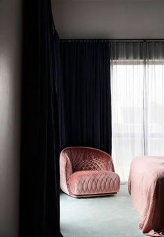 dark curtains with pink lounge chair and bedding. / sfgirlbybay