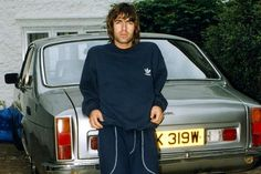 Liam Gallagher dressed in tracksuit bottoms and a matching hoodie in front of his Bristol car. Gene Gallagher, Lennon Gallagher, Liam Gallagher Oasis, Liam Oasis, Oasis Music, Bristol Cars, Liam And Noel, Oasis Band, El Rock And Roll