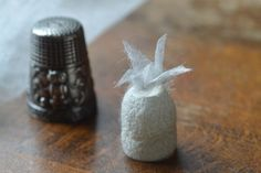 絹の折り鶴 On a cocoon is a tiny origami crane made of a thin silk sheet of 30 mm square. An origami crane symbolizes prayers and blessings. The thimble is put for size comparison.