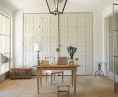 The desk and chair are French and Swedish antiques, and office supplies hide behind the antique doors, in this gorgeous home office at Patina Farm.