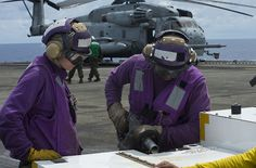 Sailors refuel equipment on flight deck. by Official U.S. Navy Imagery, via Flickr