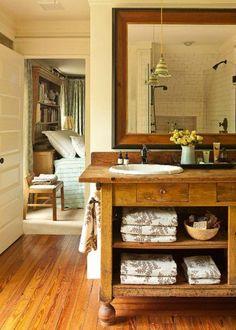 Rustic Chic Bathroom. Pine floor, vintage-table vanity, oil-rubbed bronze fittings, subway tile w/ grey grout, bookcase headboard