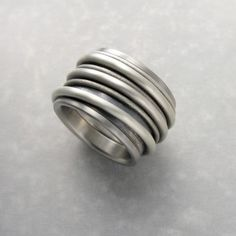 The ring is made of eleven silver and titanium elements.All parts o the ring are movable (rotating).Before purchasing please contact and check the appropriate size is available.