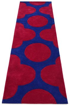 """An abstract styled bespoke rug hand tufted with pure wool in blue and red. It has a pile depth of 15-18mm. Created using the """"sufi"""" design."""