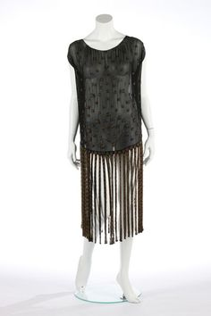 A beaded black chiffon flapper dress with 'ribbon' skirt, circa 1924. adorned with topaz-coloured seed bead roundels edged in black bugle beads, bust 112cm, 44in Gabrielle Chanel introduced a black flapper dress with ribbon hem in 1924.