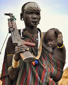 Mursi woman carrying her baby and rifle. Omo Valley, Ethiopia