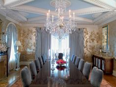 A crystal chandelier suspended from an intricately carved coffered ceiling is the focal point in this formal dining room. The gold-toned Asian style wallpaper adds an opulent, exotic look.