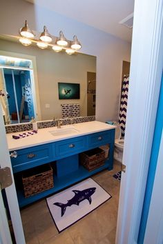 Fun shark themed bathroom with navy blue and white chevron shower curtain, shark picture, shark towels and floor mat.  A white quartz counter top with fun rock back splash.  The shower enclosure has rock starfish inlays and wavy gray stone walls.