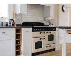 De FALCON Classic 110 gas/elektro afgebeeld in de kleur creme en geplaatst in een bijpassende keuken