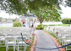 White and coral Flower Petals with jars of white hydrangea, coral roses and dahlias and variegated pittosporum line the Aisle to the gazebo where coral flower balls / pomanders hang with Navy Blue and White Chevron Ribbon by Andrea Layne Floral Design (www.andrealaynefloraldesign.com)