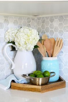 Kitchen accessories, hexagon tray, Carra marble backsplash. Beautiful white IKEA SEKTION GRIMSLOV kitchen with aqua and green accents, a gorgeous marble hexagon backsplash, and quartz countertops. | JustAGirlAndHerBlog.com