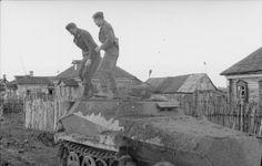 1941, Union Soviétique, Un Schützenpanzer (Sd.Kfz. 250) couvert de boue lors d'une halte dans un village