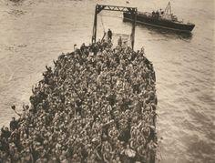 Tropas brasileiras, a caminho da praia numa barcaça britânica de desembarque, acenam adeus para seus amigos ainda a bordo do navio que os trouxe para a Itália. V Exército-Leghorn, Itália – 06/10/44