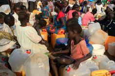 Displaced people wait for water at Tomping refugee camp