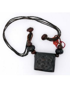 West Africa   Amulet necklace; rectangular dark brown leather charm box inscribed with geometric pattern, suspended on 4 strands of vegetable fibre terminating in leather toggles which loop through leather straps, each with 3 leather beads, attached to box.   ca. prior to 1969