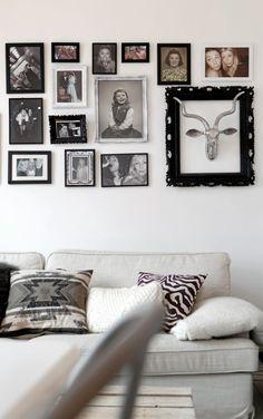 Veggen over sofaen er dekorert med gamle og nye fotografier i ulike rammer.