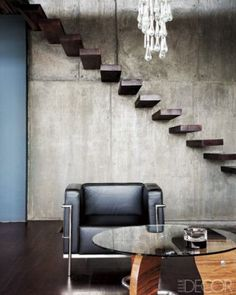 Floating steps seem to defy gravity in a couple's concrete-block house in Pretoria, South Africa. Constructed from solid Misando wood from Zambia, the stairs link the ground floor to the mezzanine level; a Le Corbusier–style chair and a glass table underscore the minimalist vibe.