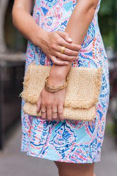 Lilly Pulitzer shell print dress + raffia clutch + gold bangles styled by Rhyme & Reason.