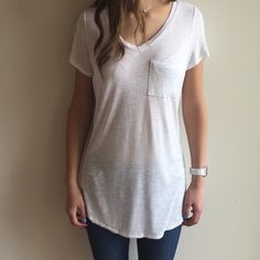 """[white V-neck short sleeved soft tee] This beautiful WHITE top has a V-neckline, breast pocket, and short sleeves. It feels so nice against the skin, and the fabric feels SUPER soft.Reminds me very much of Vince's buttery textured clothes! VERY form fitting and makes your body look amazing. 100% rayon. Size M (modeled)- 28"""" long,17""""laying flat pit to pit.Doesn't come with tags as it was purchased directly from the vendor--they are COMPLETELY new. Tops Tees - Short Sleeve"""