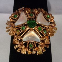 Coupon Code 050116 - Fabulous Florenza Vintage Brooch -featuring Green and Amber Rhinestones plus Mother of Pearl in the Center as well. The price of this brooch is $28. and that is before your discount.  Buy this brooch because it i a unique shape and a collector's item or Buy it as a Mother's Day Gift. Have a great vintage day! Best, Coco