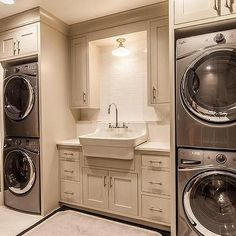 Contemporary Laundry Room with two Sets of Stacked Washers and Dryers Flanking Sink