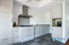 Handgemaakte landelijke keuken met terrazzo aanrechtblad, gas op glas en tegeltjes spoelbak.