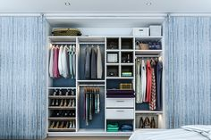"""White and Chocolate Linen melamine creates contrast in this reach-in closet. Boasting pressed glass sliding doors with a blue organic design, 16"""" deep panels, shelves and drawers, and chocolate melamine lined cubbies to create contrast, this women's reach-in closet is the epitome of modern style."""