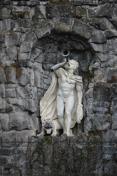 A statue at the base of the Hercules monument in Wilhelmshöhe Park in Kassel, Germany