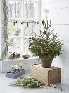 Nordic Christmas decor with an evergreen tree with pinecones in a basket, a pinecone and candle chandelier, greenery, lights and bulbs - DigsDigs Winter Wonderland Christmas, Nordic Christmas, Natural Christmas, Christmas Minis, Rustic Christmas, Simple Christmas, Beautiful Christmas, Primitive Christmas, Christmas Snowman