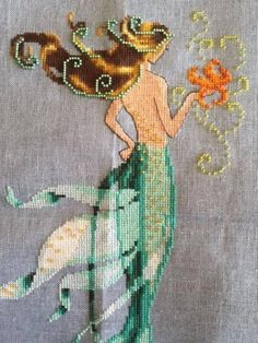 Mai Soli is the title of this cross stitch pattern from Nora Corbett's La Petite Mermaids Collection. Click on highlighted link to add the embellishment pack to your shopping cart. The second photo is the stitched model and used with permission of the designer.