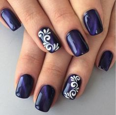 Simple yet elegant looking dark blue nail art design. The dark blue nail polish that serves as the background is then topped by a white nail polish in tribal inspired shapes.