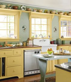 The kitchen gets its warmth from cherry counters, an antique island, gingham-check wallpaper, and an its yellow cabinets. Free up cabinet space, and create a clever spot for collectibles, with above-window shelving.   - CountryLiving.com