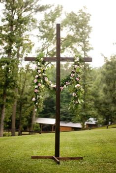 The cross will be draped with a greenery garland with pops of blush and ivory spray roses, and finesse roses.