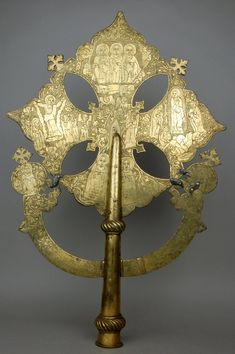Processional cross. Ethiopia. 1721-1730 silver, gold, cast bronze; soldered, punched, gilded, and engraved. The Holy Trinity surrounded by a winged bird, ox, lion and a man representing the four living creatures and the throne of God. Directly below is Emperor Bakaffa prostrate.