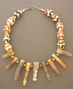 The individual beads of fossil bamboo that make up this  necklace are millions of years old, and their unique colors, patterns, and  shapes will guarantee you something to talk about for years to come. Fresh  water pearls and ten large ceramic beads, with a fancy sterling silver hook  and eye clasp that was handmade in Sri Lanka, complete this necklace.