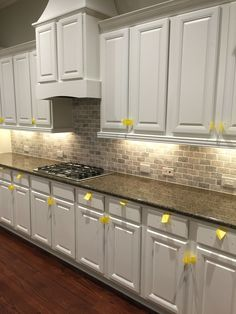 Anna Berry Design, LLC - painted sherwin Williams Dover White finish cabinets, travertine Claris tile, and raised cabinet tops..