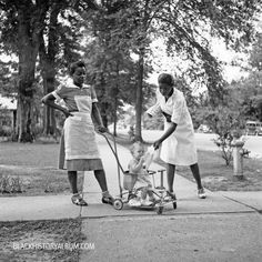 A pair of American house maids/nannies taking a baby for a stroll, Port Gibson, Mississippi, 1940.