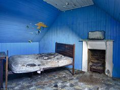 This blue bedroom was photographed on South Uist - a mirror remains over the fireplace and...