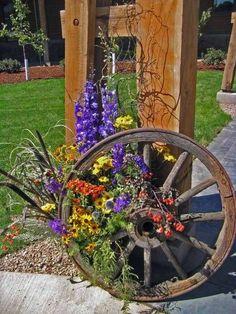 Mountain Wedding 30 Rustic Country Wedding Ideas with Wagon Wheel Details Wagon Wheel Garden, Wagon Wheel Decor, Wedding Flower Arrangements, Wedding Flowers, Old Wagons, Rustic Flowers, Yard Art, Garden Projects, Wagon Wheels
