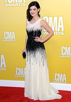 The Pretty Little Liars actress styled a white-lace, cowl-neck Moschino gown with black sequins and carried Kotur.