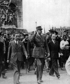 A beaming General de Gaulle marches down the Champs-Elysses. Top aide Alexandre Parodi is on his left.