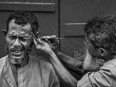 """Careful, brother... (Kolkata, India) by Sandipan Mukherjee. """"Travellers to the city may still seek out vestiges of the Kolkata of yore in the labyrinthine streets of Bagbazar. In some quaint little alley, one may even chance upon an itinerant kaan-saaf-wallah (ear-cleaner), armed with his strange array of tools, attending to a terrified customer."""""""