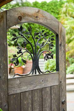 Iron fruit tree insert in wooden garden door.   followpics.co
