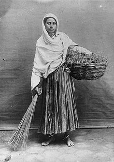 Studio portrait of young woman with basket and broom, India | by UW Digital Collections