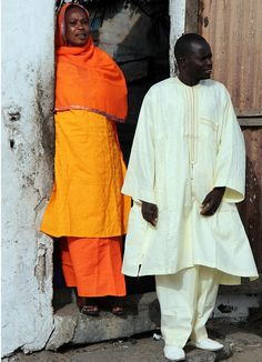 A brightly dressed couple wait at the entrance to their yard. Saint-Louis #senegal