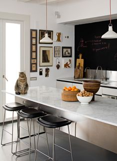 blackboard, stainless steel splash back, marble bench top, stainless steel cabinets, bar stools tucked under kitchen island, low hanging lights.